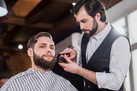 handsome young barber shaving man with Hair Cutting Machine Фото со стока