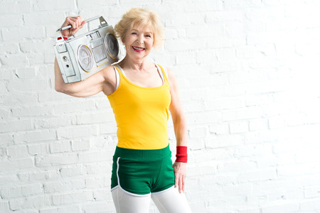 cheerful senior sportswoman holding tape recorder and smiling at camera