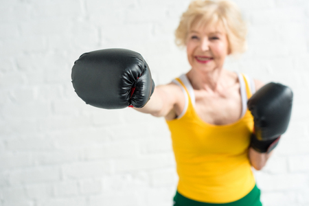 close-up view of smiling senior woman boxing in gloves selective focuscopy space Archivio Fotografico