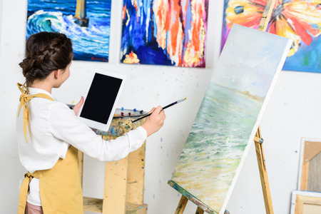 side view of kid looking at tablet and painting on canvas in workshop of art school Фото со стока
