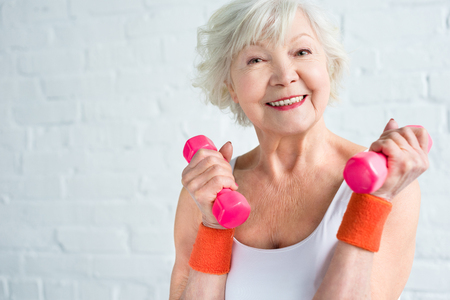 happy senior woman exercising with dumbbells and smiling at camera
