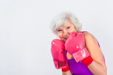beautiful senior woman in boxing gloves smiling at camera isolated on grey