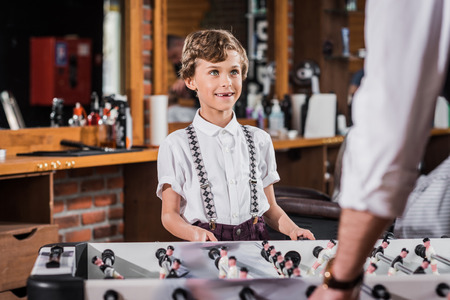 happy little kid playing table football with father