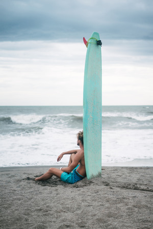 surfer sitting on sandy beach and leaning on surfboard in Bali, Indonesia