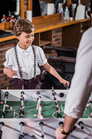 adorable little kid playing table football with father