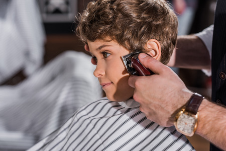 adorable curly kid getting haircut with Hair Clipper Stockfoto