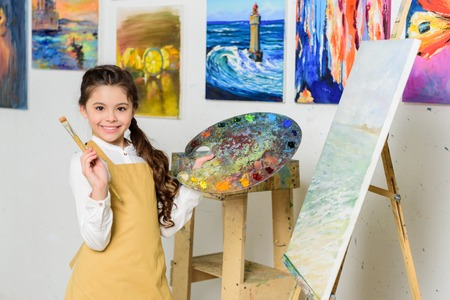 smiling kid holding painting brush and canvas in workshop of art school Фото со стока