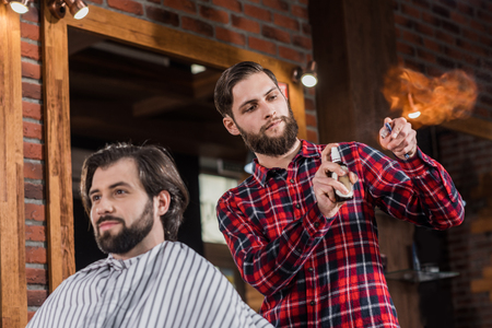 young barber spraying disinfectant onto straight razor before shaving Stok Fotoğraf - 106826112