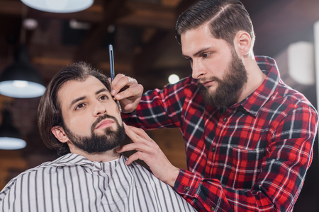 confident young barber in plaid shirt shaving man with Hair Cutting Machine