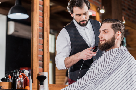 handsome confident barber shaving man with Hair Cutting Machine