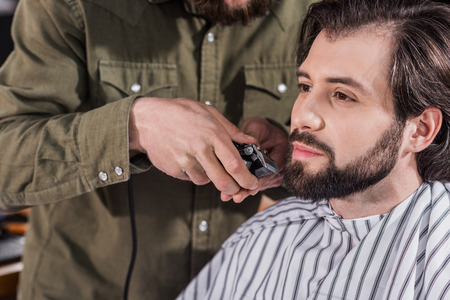 cropped shot of barber shaving client with Hair Clipper