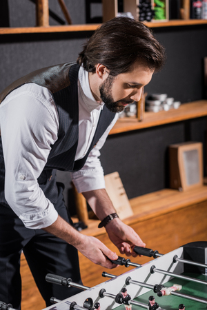handsome bearded man in vest playing table football Stock Photo