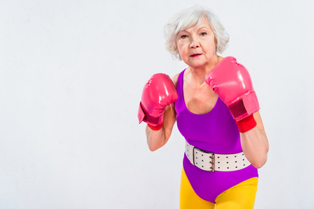 senior woman in sportswear and boxing gloves looking at camera isolated on grey