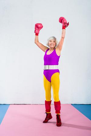 cheerful senior female boxer raising hands and smiling at camera