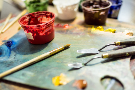 painting brushes, palette and poster paints on wooden table in workshop 写真素材 - 106826325