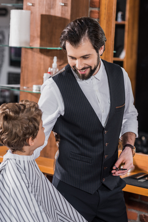 handsome happy barber talking to little kid while he sitting in chair at kids barbershop Banco de Imagens