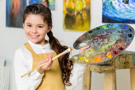 smiling kid pointing on palette with painting brush in workshop of art school