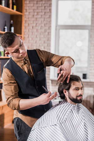 bearded young man covered with striped cloth getting haircut from professional barber at barbershop Фото со стока