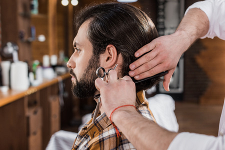 side view of handsome man getting haircut in barbershop Фото со стока