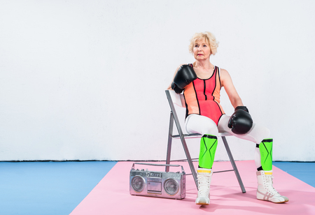 sportive senior woman in boxing gloves listening music and looking away