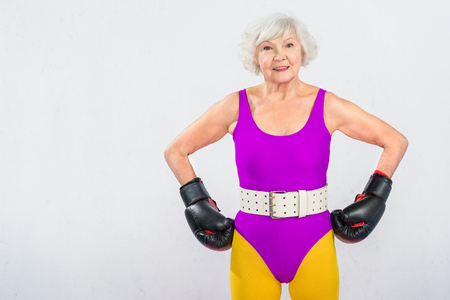happy senior sportswoman in boxing gloves standing with hands on waist and smiling at camera isolated on grey Stock Photo