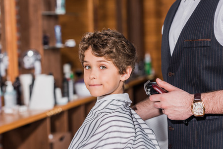 little curly kid covered with striped cloth sitting at barbershop while barber standing nearby Stockfoto