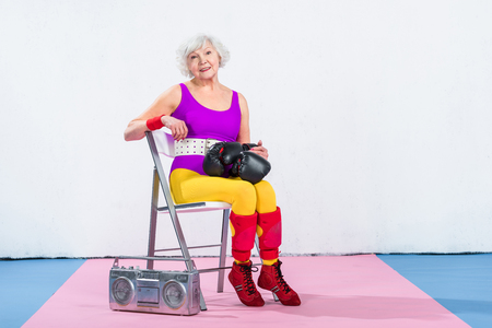 happy sporty senior woman with boxing gloves sitting and smiling at camera