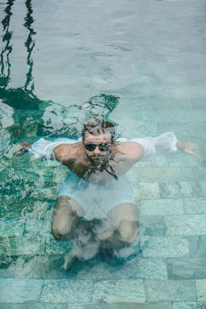 man in sunglasses under water in swimming pool in Bali, Indonesia