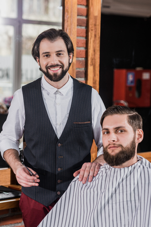 smiling bearded barber with client at barbershop Фото со стока - 106827702