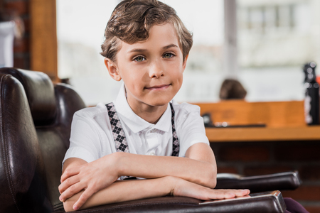 little kid sitting in barber chair at barbershop and looking at camera