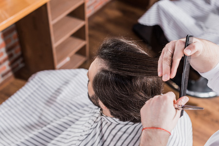 high angle view of barber cutting hair of client with scissors Фото со стока