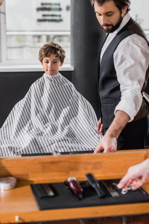 mirror reflection of barber preparing to cut hair of little kid