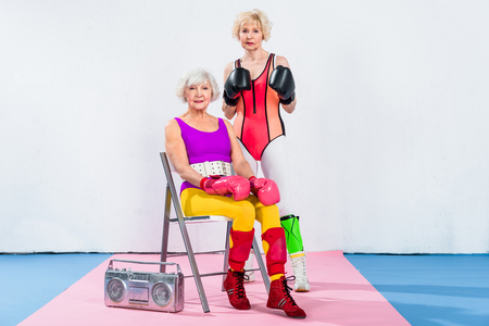 sporty senior women in boxing gloves looking at camera during workout