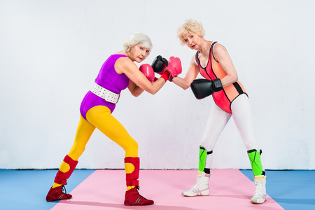 full length view of senior sportswomen in boxing gloves training and looking at camera