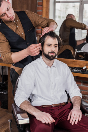 young barber combing hair of customer at barbershop Фото со стока - 106828190