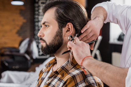 side view of bearded man getting haircut in barbershop Фото со стока