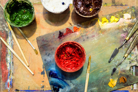 top view of painting brushes, palette and poster paints on wooden table in workshop 写真素材 - 106828254