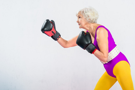 side view of sporty senior lady in sportswear boxing isolated on grey