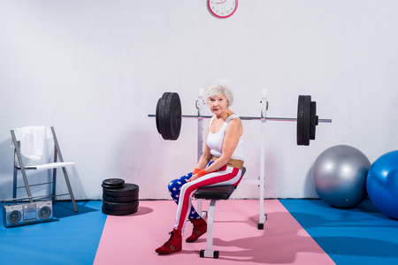 sportive senior lady in sportswear sitting and looking at camera in gym