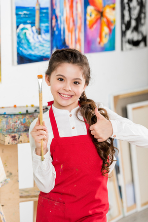 kid showing thumb up and holding painting brush in workshop of art school Imagens
