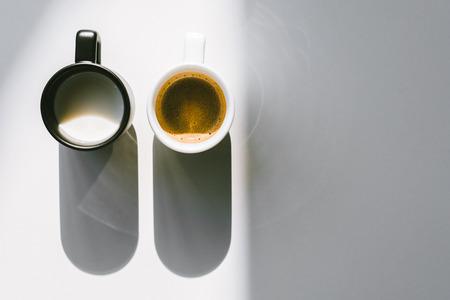Vue de dessus des tasses de lait et de café en noir et blanc sur une table blanche