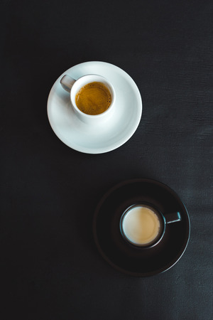 high angle view of black and white cups of milk and coffee on black surface Banco de Imagens