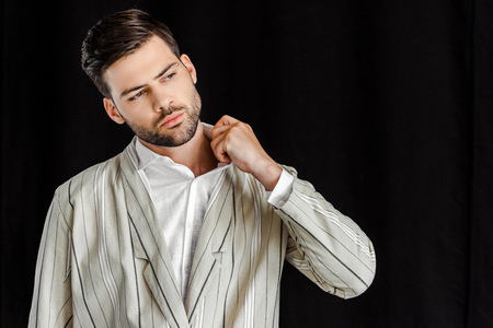 attractive young man in stylish striped jacket isolated on black Stock Photo