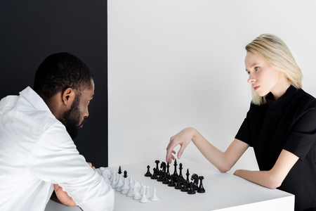 multicultural couple playing chess near black and white wall Stock Photo