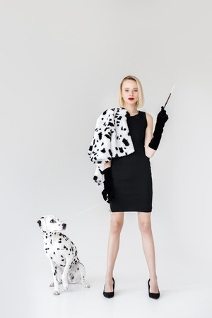 attractive stylish blonde woman in black dress holding cigarette, dalmatian dog on floor Banco de Imagens