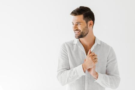 zijaanzicht van de glimlachende man in linnen wit overhemd dat op grijze achtergrond wordt geïsoleerd