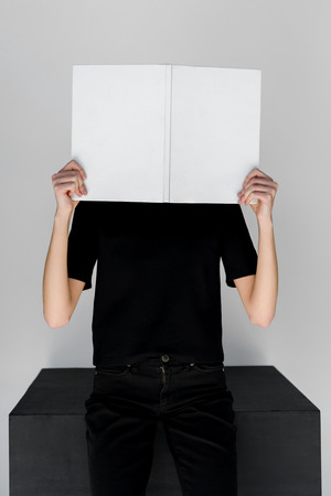 stylish woman in black clothes covering face with white book isolated on grey Stock fotó