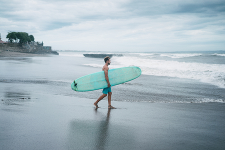 side view of surfer walking with surfboard in Bali, Indonesia