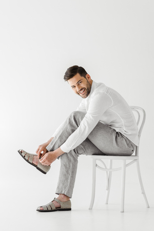 smiling man in linen clothes sitting on chair and putting on sandals isolated on grey background Standard-Bild - 106866514