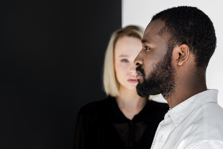 side view of handsome african american boyfriend standing in front of blonde girlfriend
